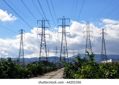 Electric power line towers against cloudy blue sky.