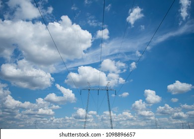 Electric power lines and a beautiful blue sky with white puffy clouds