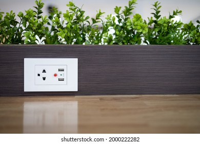 Electric power outlet socket with built in USB chargers on the table between seats for charging students' mobile phones or plugging in electrical appliances in restaurant or dining room at school