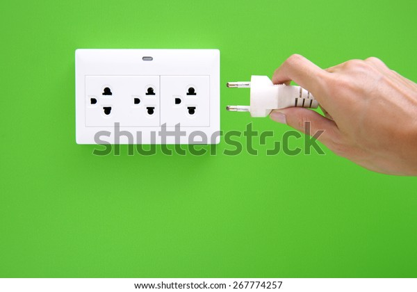 Electric power plug in a hand and inserting into power wall socket