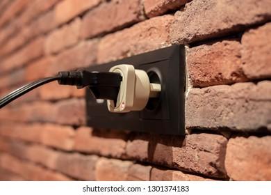 Electric power plug plugged into a brick wall socket