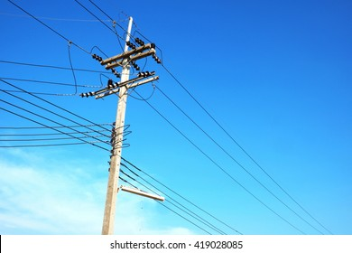 Electric power post with wire and clear blue sky.