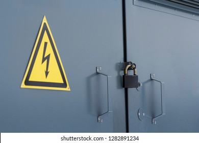 Electric power substation with attention sign. Closed lock