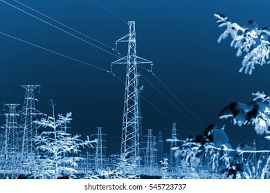 Electric power tower and trees in the snow, closeup of photo