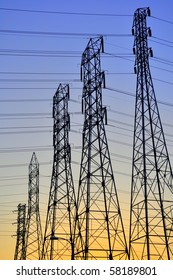 Electric power towers silhouetted against the sunset.