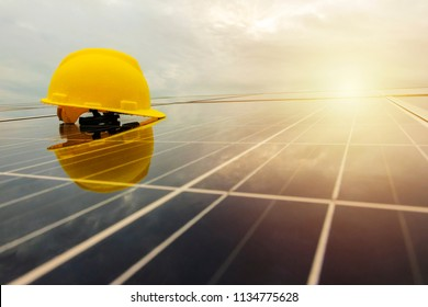 Electric power is very necessary. Make use of your own electricity by using solar panels. Engineer helmet put on photovoltaic.Rainy in the sunset.