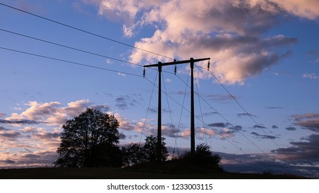 Electric pylon silhouetted against an evening sky