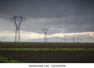 Electric pylons leading into a stormy sky, Italy