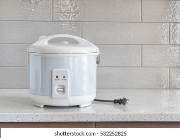 Electric rice cooker on granite counter-top against ceramic backsplash