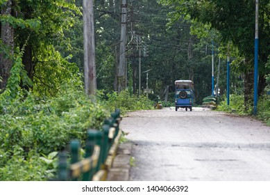 An electric rickshaw is moving through a textured road in green nature