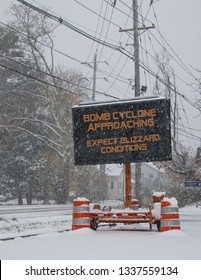 Electric road traffic mobile sign by the side of a snow covered road with snow falling warning of BOMB CYCLONE approaching, expect blizzard conditions