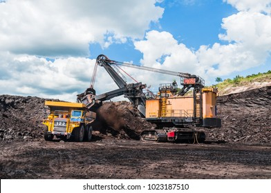 Electric rope shovels loading of coal, ore on the dump truck. The big dump truck is mining machinery, or mining equipment to transport coal from open-pit or open-cast mine as the Coal Production.