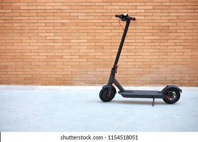 Electric scooter, brick wall