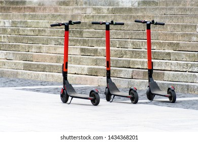 Electric scooters in row on the parking lot. City bike rental system, public kick scooters on the street.