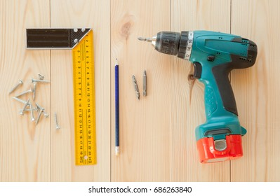 Electric screwdriver, roulette and handsaw at wooden desk background