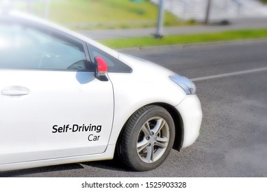 electric self driving car test vehicle with self-driving car lettering on side of door moving along modern city street closeup view blurred background concept of new automobile autopilot technology