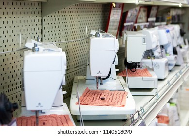Electric sewing machines on store shelf, side view, shallow depth of field. Product for hobbies. For sewing clothes at home.
