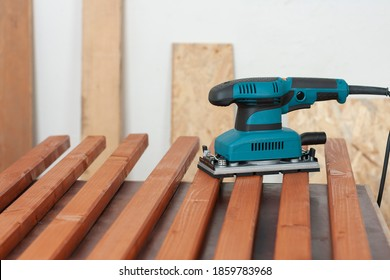 Electric sheet finishing sander on wooden slats for production of  wooden garden bench on table in carpentry  workshop