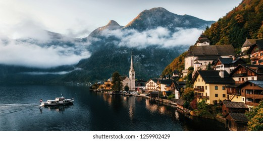 Electric small ferry arrives at pier of Hallstatt town reflecting in Hallstattersee lake in Austrian Alps in morning, Salzkammergut region, Austria