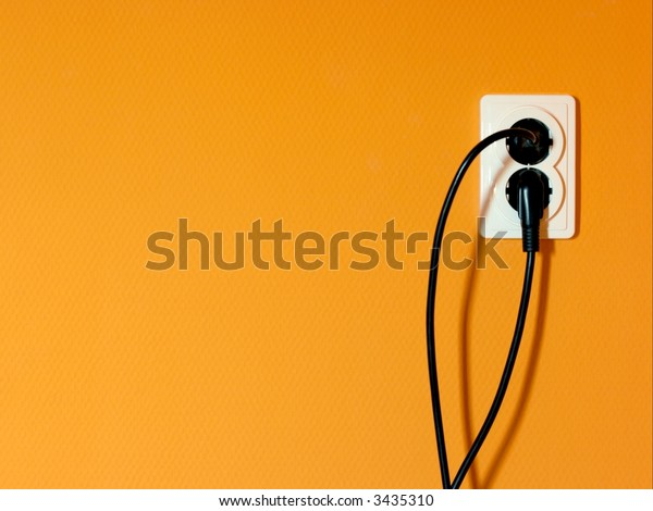 Electric socket on an orange wall with connected cables