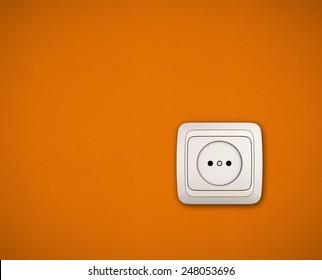 Electric socket. Simple white electric socket on orange wall.