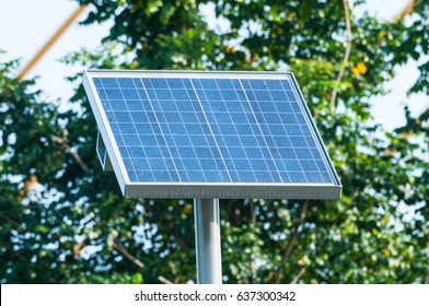Electric Solar cell, solar energy, photovoltaic panel on background of green area. Solar Energy is clean energy to safe world