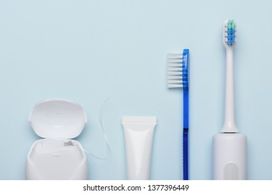 Electric sonic toothbrush with dental floss toothpaste and classic tooth brush on blue background flat lay.