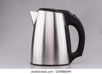 Electric stainless steel kettle on clear grey background.