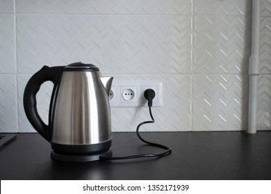 Electric stainless steel kettle on a granite counter top against a ceramic background