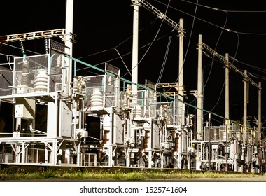 Electric substation with high-voltage equipment - isolators, bearings, transformers, wires, etc. at night