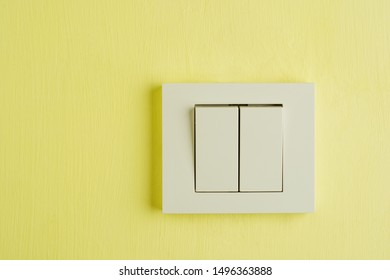 Electric switch with space for text on yellow wall.