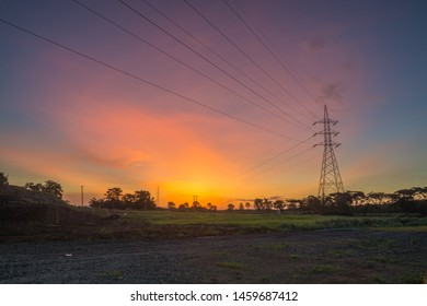 Electric Tower with Cable against Twilight Sky with blue, orange and red Color.