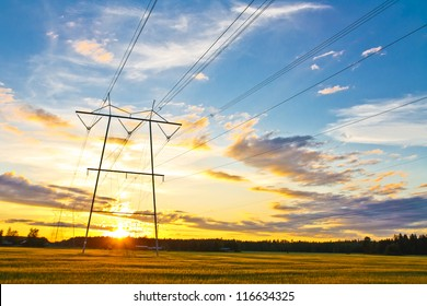 Electric towers on a field with sunset