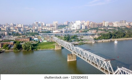 The electric train crosses the Ob river. First Railway Bridge in Novosibirsk. Panorama of the city of Novosibirsk. Russia, From Dron