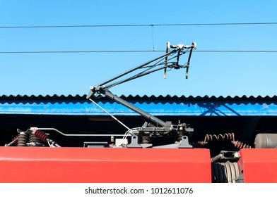 Electric train trolley pole railway electrification system with wires and blue sky above