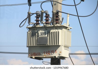Electric tranformer installed on the eletric ploe tower while electric cables crossing blue clouds in the sky in thailand