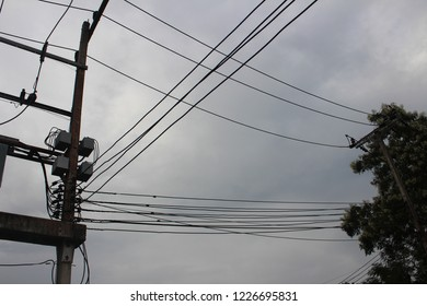 Electric tranformer installed on the tower while electric cables crossing under the dark clouds in the sky