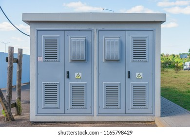 Electric Transformer room  building with grey doors and yellow hazard signs on blue sky background