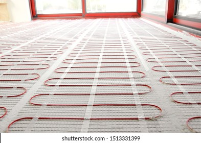 Electric underfloor heating red mats on cement floor. Heating red electrical cable on cement floor copy space background. Renovation and construction, comfortable warm home concept.