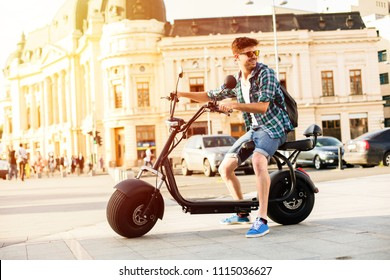 Electric urban transportation. young man ready to ride his electric bike with his backpack in the back, smiling on a sunny day, in the center of a city