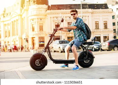 Electric urban transportation. Young man with sunglasses sitting on electric vehicle, scooter, in the center of a metropola