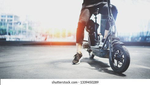 Electric urban transportation.Young man ready to ride his electric scooter bike in the center of a city. Wide.