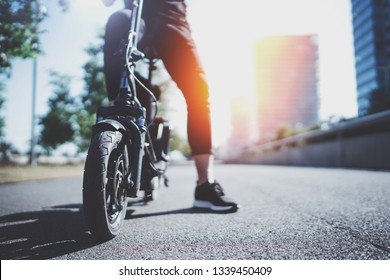 Electric urban transportation.Young man ready to ride his electric scooter bike in the center of a city. Innovative transport