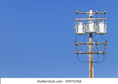 Electric utility pole with 3 transformers. Wooden post with high voltage signs, power distribution lines. Room for text, copy space. Blue sky background.