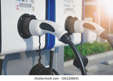electric vehicle charging (Ev) station with plug of power cable supply for Ev car. Smart enegy.Flare light effect