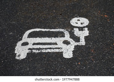 An electric vehicle charging point sign painted on the surface of a car park at Tenterden in Kent, England.