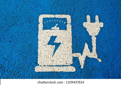 Electric vehicle charging public station sign on blue painted asphalt .
