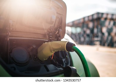 Electric vehicle charging station. Charging an electric car with the power cable supply plugged in. Eco-friendly car for environment