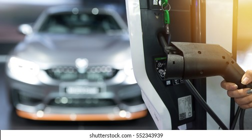 Electric vehicle charging station for home with EV car background , Flare light