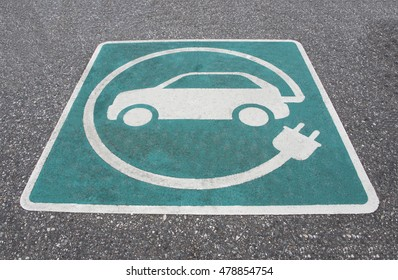 Electric vehicle charging station sign on asphalt in public area